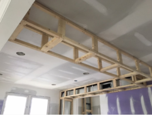 The interior ceiling of a house in which drywall is being installed.