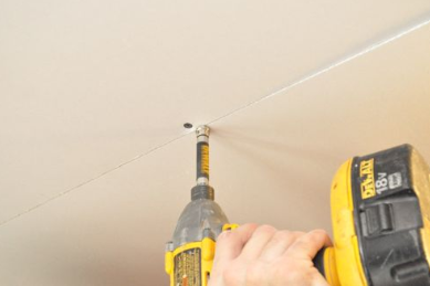 A drill being used on a ceiling.
