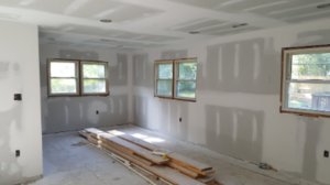 The dining room of a house that has just finished being drywalled.